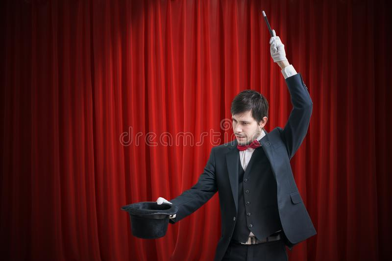 Happy magician or illusionist is showing magic trick with his wand. Red curtains in background stock photography