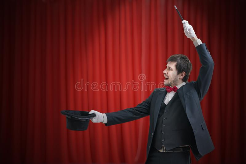 Happy magician or illusionist is showing magic trick. Red curtains in background royalty free stock image