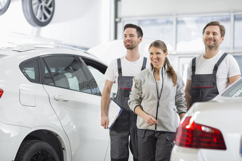 Download Happy Maintenance Engineers Looking Away In Automobile Repair Shop Stock Photo - Image: 41407390