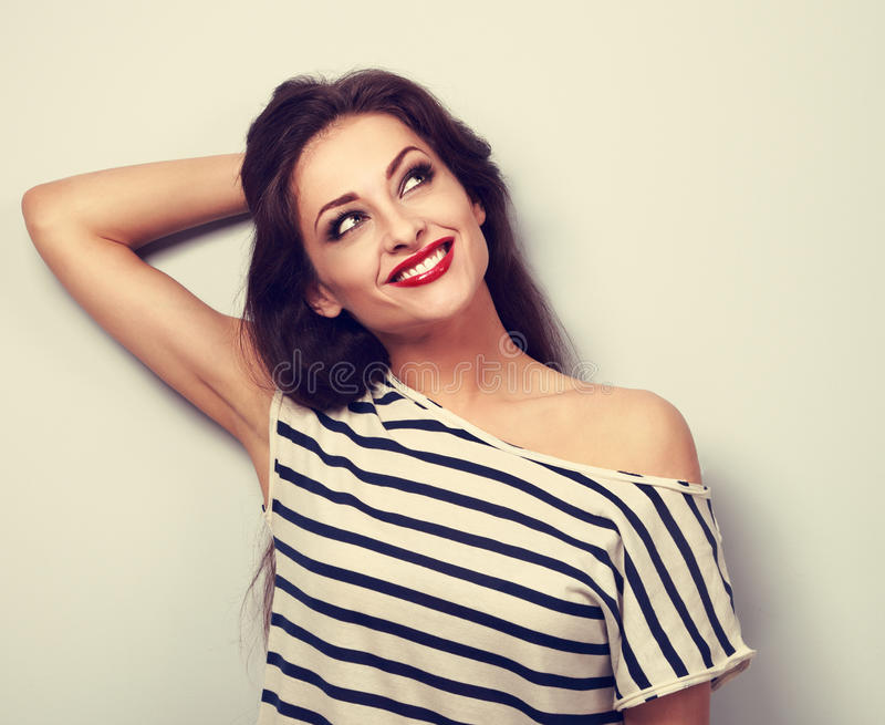 Happy makeup thinking young woman relaxing and looking up. Bright toned closeup portrait with empty space stock photo