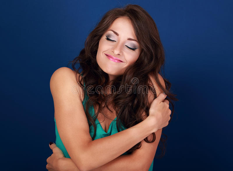 Happy makeup woman hugging herself with natural emotional enjoying face. Love concept of yourself body and face on blue background royalty free stock photo