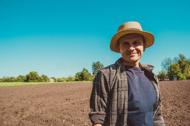 Happy male agro tourist in hat. Authentic rural farmer portrait. Agriculture worker. Vegetable garden. Rustic background. Country. Man. Manual labor. European royalty free stock photo