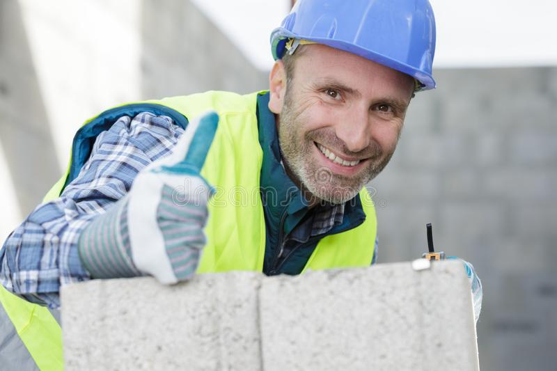 Happy male builder showing thumb up stock image