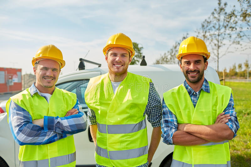Happy male builders in high visible vests outdoors. Industry, building, construction and people concept - happy male builders in high visible vests outdoors royalty free stock photos