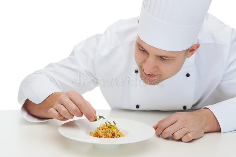 Happy male chef cook decorating dish. Cooking, profession, haute cuisine, food and people concept - happy male chef cook decorating dish royalty free stock images