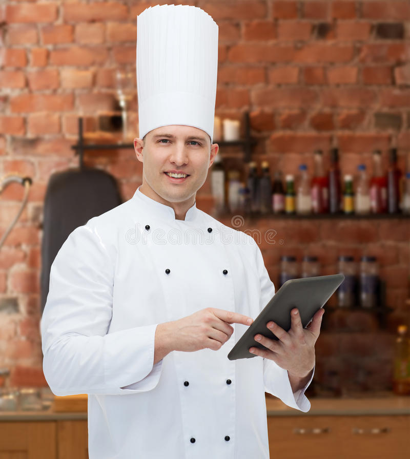 Happy male chef cook holding tablet pc. Cooking, profession and people concept - happy male chef cook holding tablet pc computer over kitchen background royalty free stock photography