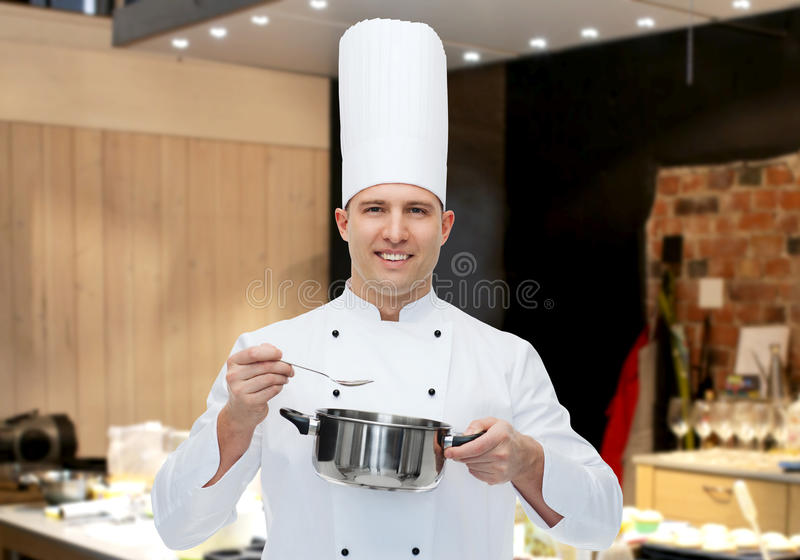 Happy male chef cook with pot and spoon. Cooking, profession and people concept - happy male chef cook with pot and spoon over restaurant kitchen royalty free stock photos