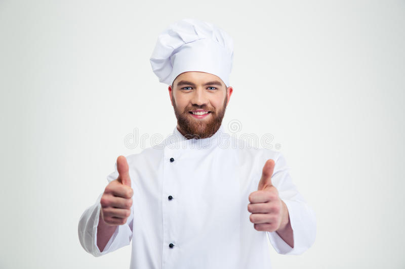Happy male chef cook showing thumbs up. Portrait of a happy male chef cook showing thumbs up isolated on a white background royalty free stock photography