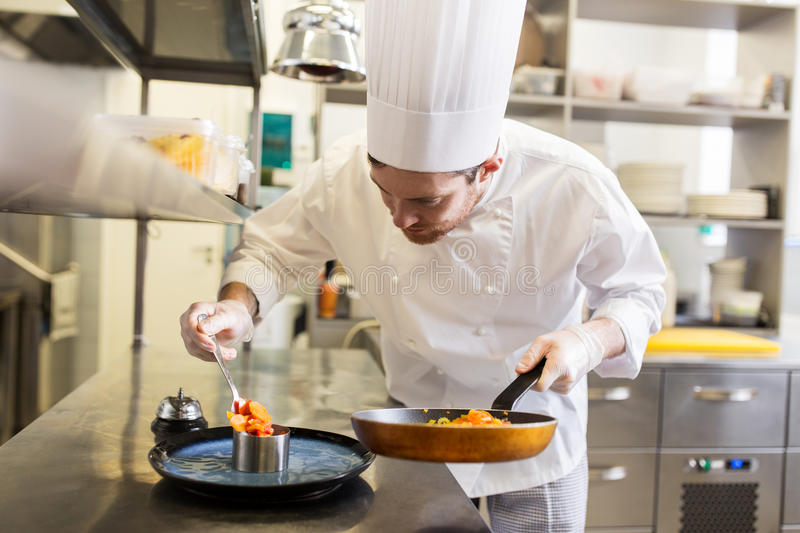 Happy male chef cooking food at restaurant kitchen. Food cooking, profession and people concept - happy male chef cook with frying pan and spoon serving stewed stock image