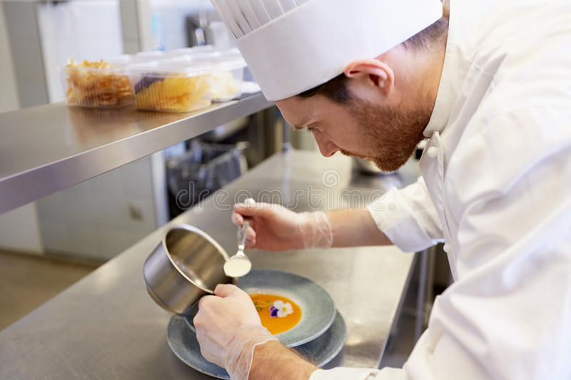 Happy male chef cooking food at restaurant kitchen. Food cooking, profession and people concept - happy male chef cook serving plate of soup at restaurant stock photography