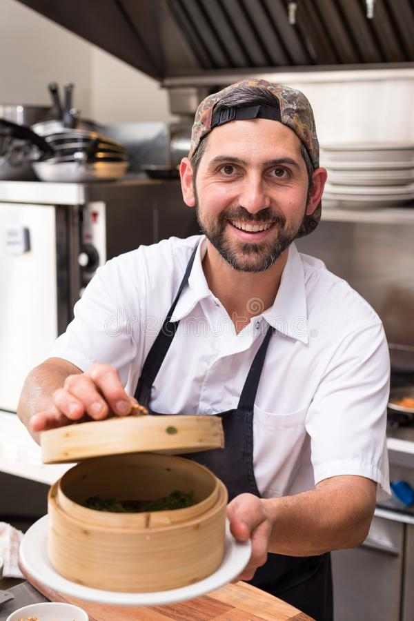 A happy male chef in a restaurant kitchen holding a bamboo dim sum steamer and smiling. royalty free stock photo