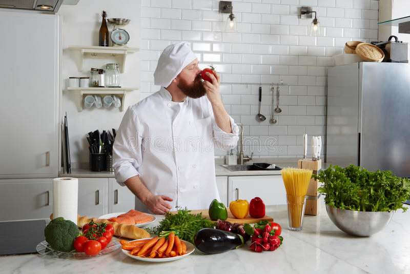 Happy male chef smell aroma of fresh tomato stock image for Fresh chef kitchen