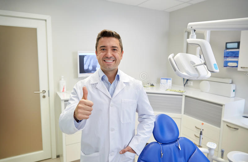 Happy male dentist showing thumbs up at clinic royalty free stock images