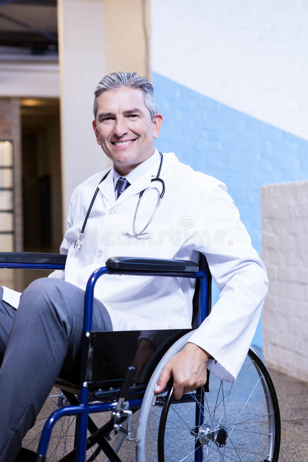 Happy male doctor sitting on wheel chair. Portrait of happy male doctor sitting on wheel chair in hospital stock image