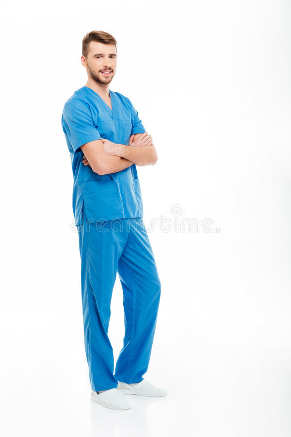 Happy male doctor standing with arms folded. Full length portrait of a happy male doctor standing with arms folded isolated on a white background stock images