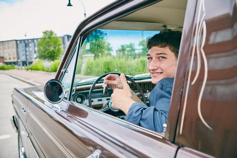 Happy male driver showing keys in open car window. Face of happy male driver sitting in car, showing keys in car window, looking at camera and smiling royalty free stock photos
