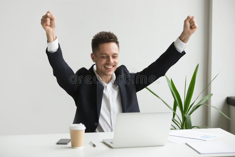 Happy male employee celebrating good online result looking at la. Happy millennial businessman raising hands feeling joy celebrating success or good online royalty free stock photos