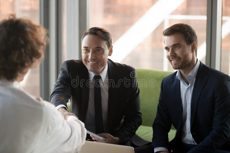 Smiling HR managers handshake job applicant greeting with success. Happy male employers shake hand of job applicant greeting him with occupied position, smiling stock photo