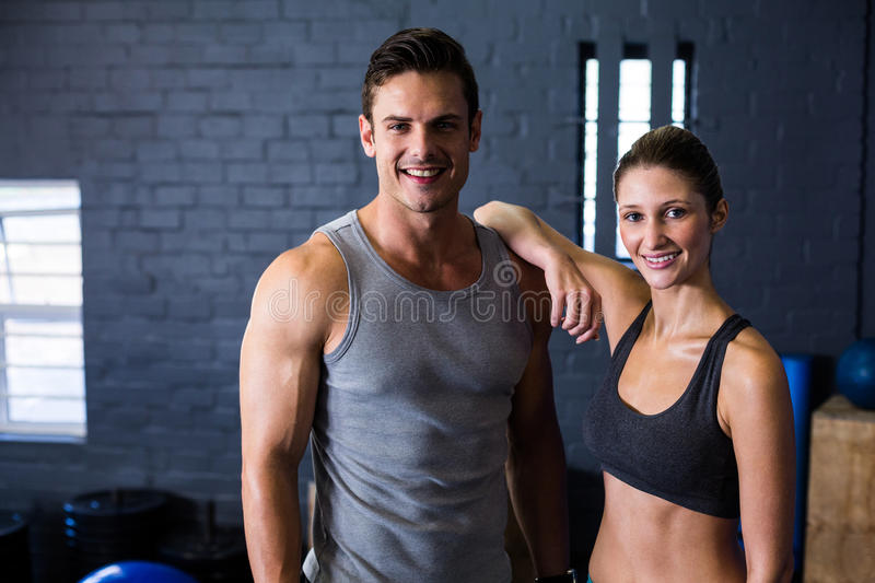 Happy male and female athlete in gym. Portrait of happy male and female athlete standing against wall in gym stock image