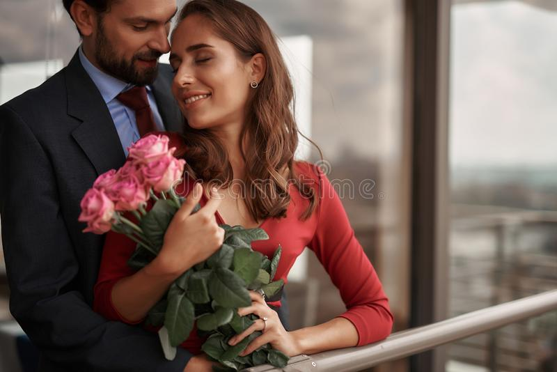 Happy male and female having romantic meeting. Concept of romantic engagement. Happy beloved lady with pink roses and diamond ring on finger embracing tenderly royalty free stock images