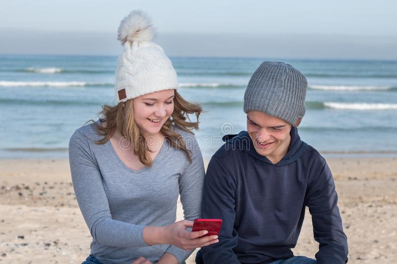 Happy male and female models wearing knitted beanies with Bluetooth speakers stock image