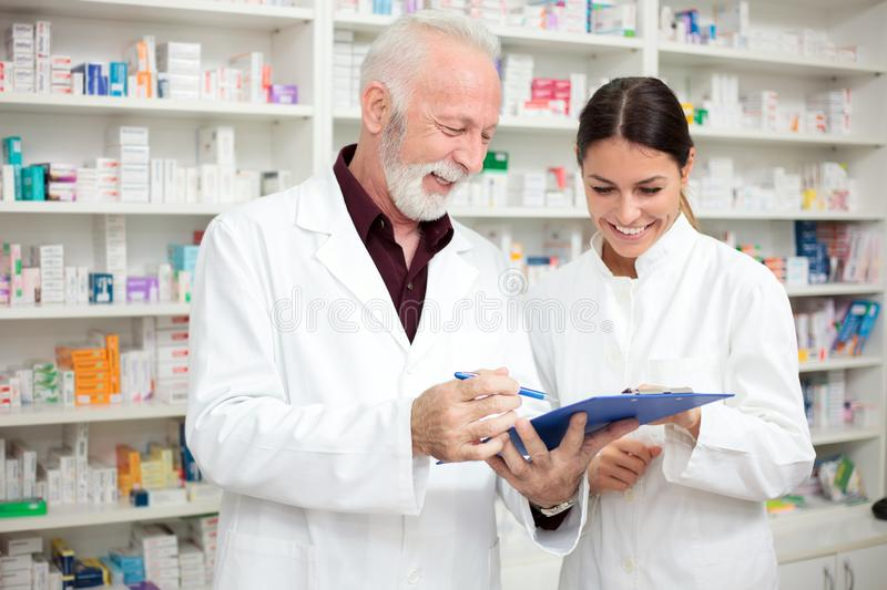 Happy male and female pharmacists holding a clipboard and writing. Medicine, pharmaceutics, health care and people concept - Smiling young female and senior male royalty free stock image