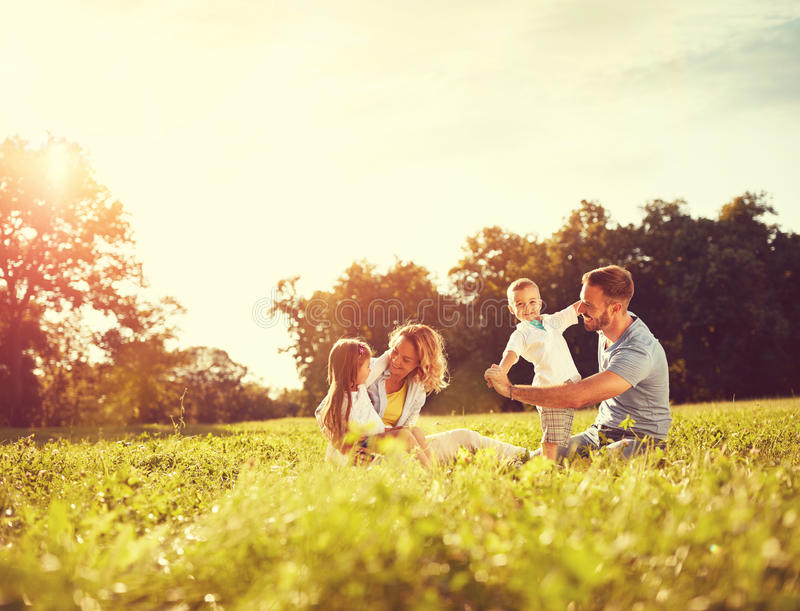 Male and female playing with children outside royalty free stock photo