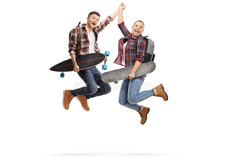 Happy male and female students holding longboards and jumping isolated on white background stock photos