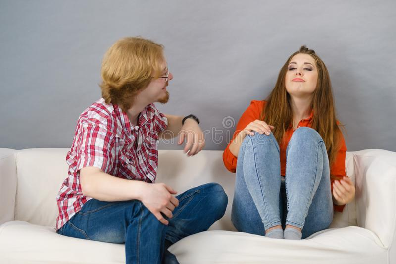 Happy man and woman sitting on sofa stock image