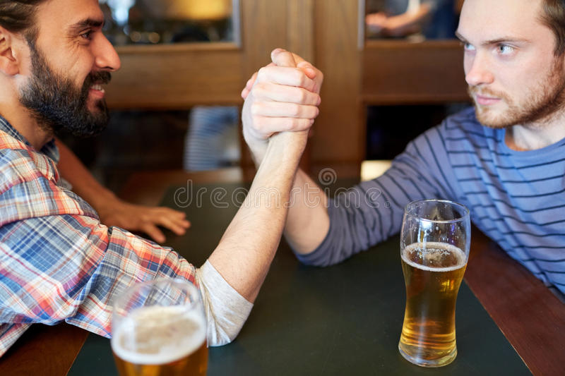 Happy male friends arm wrestling at bar or pub. People, leisure, challenge, competition and rivalry concept - happy male friends arm wrestling and drinking draft royalty free stock image