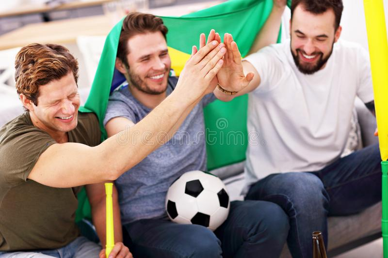 Happy male friends cheering and watching sports on tv stock image