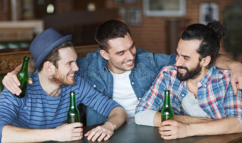 Happy male friends drinking beer at bar or pub. People, leisure, friendship and bachelor party concept - happy male friends drinking bottled beer and talking at royalty free stock image