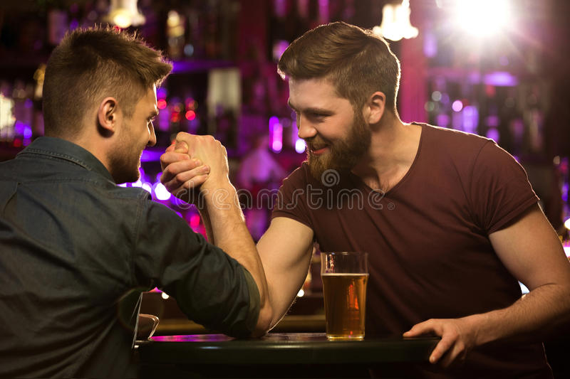 Happy male friends drinking draft beer and arm wrestling. At bar or pub stock photo