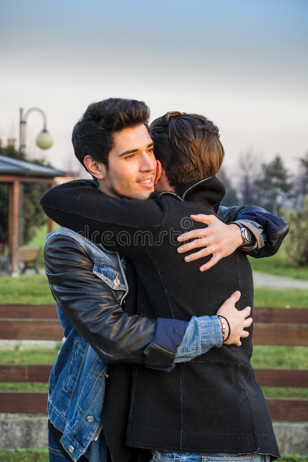 Happy Male Friends Hugging In Sunlight Stock Image - Image ...