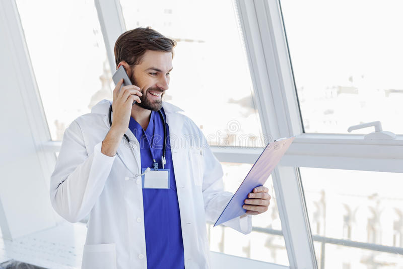 Happy male general practitioner talking on mobile stock photography