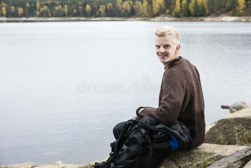 Happy Male Hiker Sitting On Lakeshore stock photos