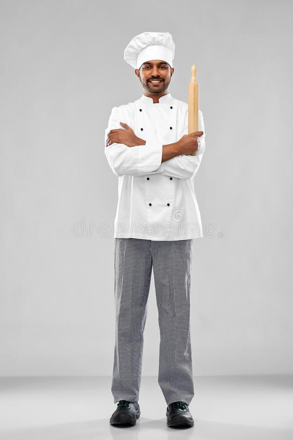 Happy male indian chef or baker with rolling-pin. Cooking, profession and people concept - happy male indian chef or baker in toque with rolling-pin over grey stock photo
