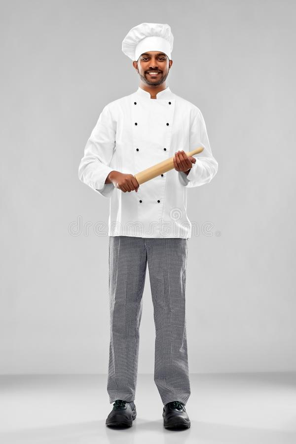 Happy male indian chef or baker with rolling-pin royalty free stock images
