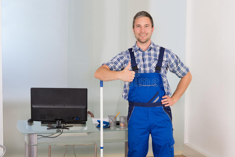 Happy male janitor gesturing thumbs up royalty free stock image
