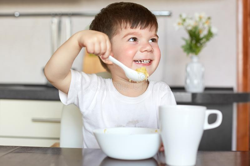 Happy male kid in casual t shirt eats delicious porridge, drinks compote, has healthy eating, sits at table against kitchen interi stock images