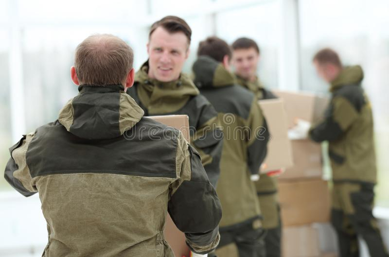 Happy male movers in uniform carrying boxes royalty free stock photos