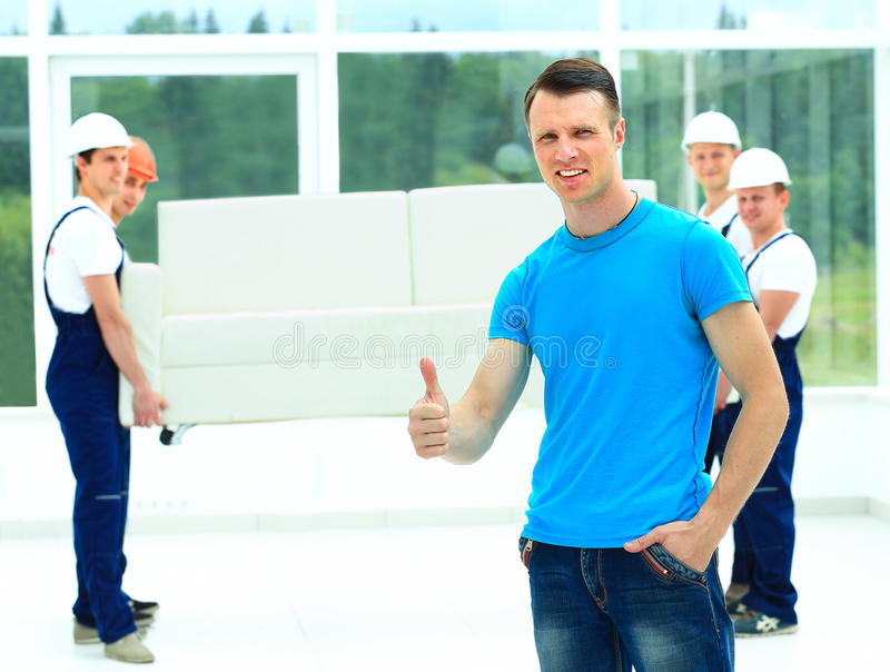 Happy male movers in uniform carrying royalty free stock photography