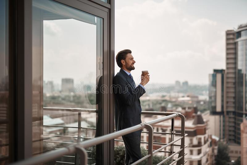 Happy male in office suit standing on balcony. Take a pause. Full length portrait of cheerful businessman leaning on french window while standing on balcony with stock photo