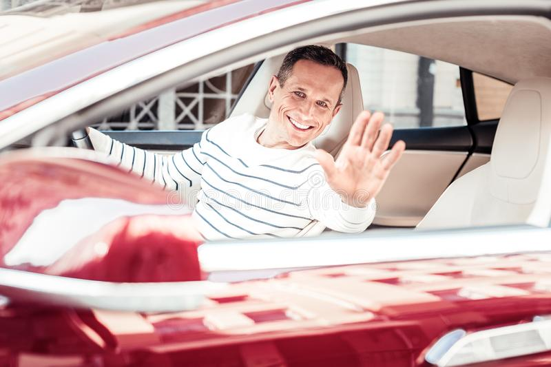 Happy male person waving his hand. Follow me. Attractive brunette man expressing positivity while sitting in his auto and looking for his friend stock photo
