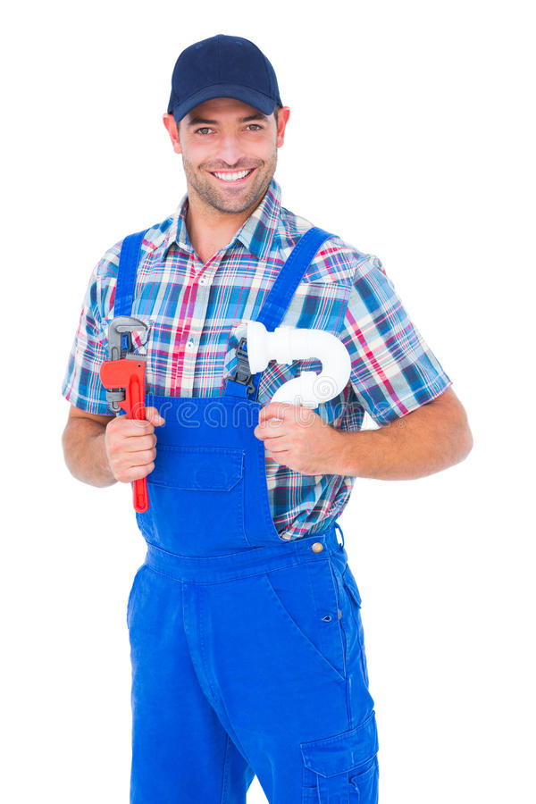 Happy male plumber holding monkey wrench and sink pipe. Portrait of happy male plumber holding monkey wrench and sink pipe on white background royalty free stock photo