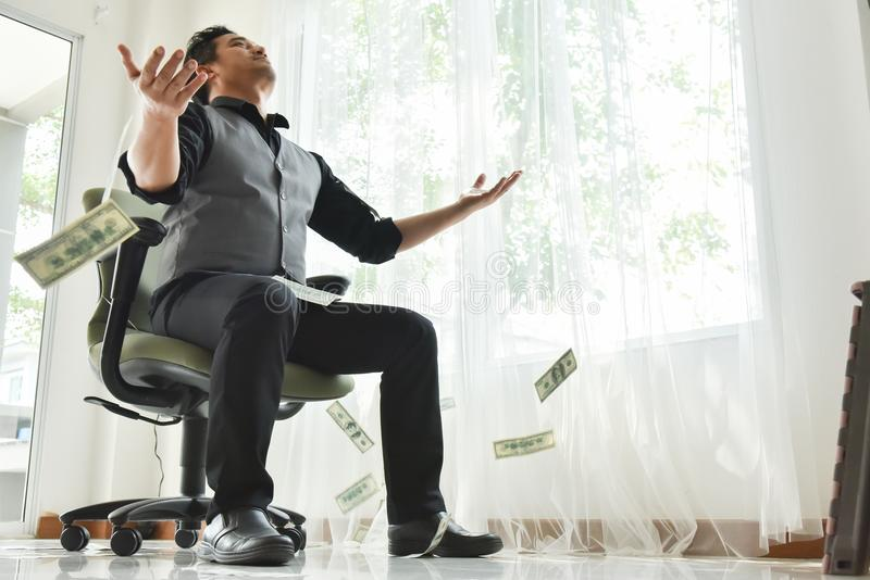 Happy male in a rain of money. Asian businessman with dollar bills cash falling down. Success economy concept. Happy male in a rain of money stock images