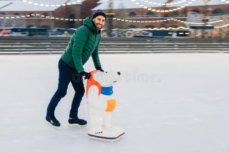 Happy male stands on ice ring on skates, leans on special aid for skating, has joy, poses at camera with happy expression. royalty free stock image