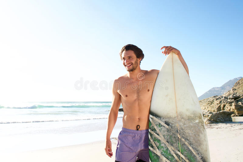Happy male surfer standing with his board at the beach. Portrait of happy male surfer standing with his board at the beach royalty free stock photography
