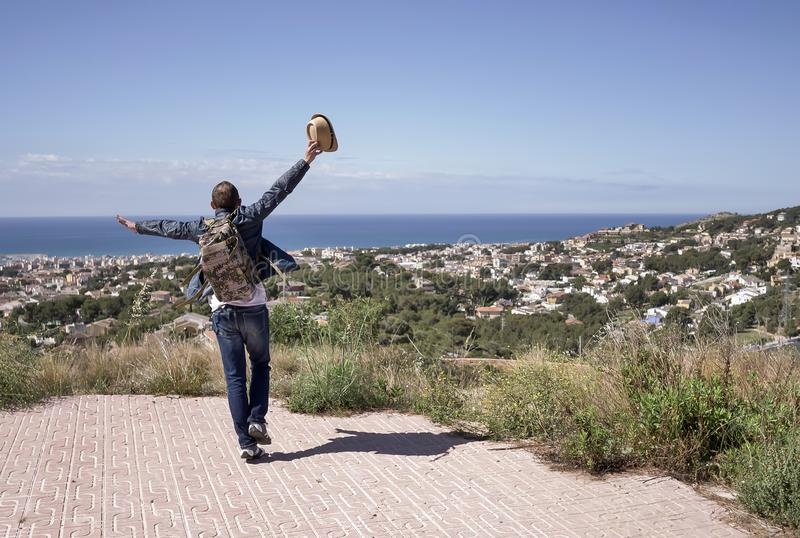 Happy male tourist dancing on the mountain near the city, copy space royalty free stock image