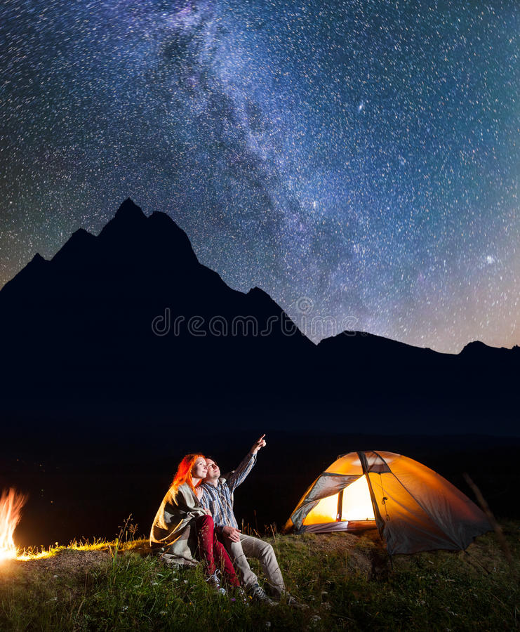 Happy male tourist showing his female at the stars in the night sky. Couple sitting near the glowing tent and campfire stock photo